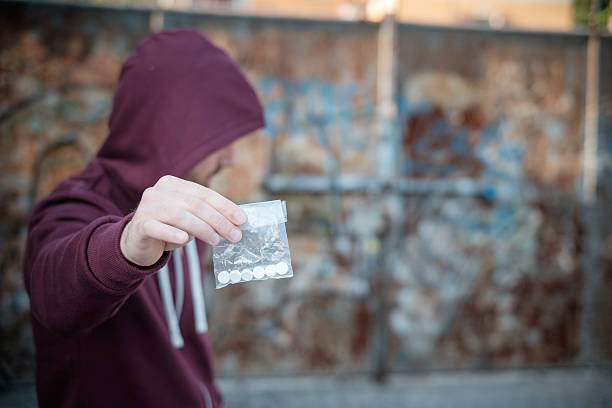 Pusher selling and trafficking drug dose Pusher selling and trafficking drug dose drug dealer stock pictures, royalty-free photos & images