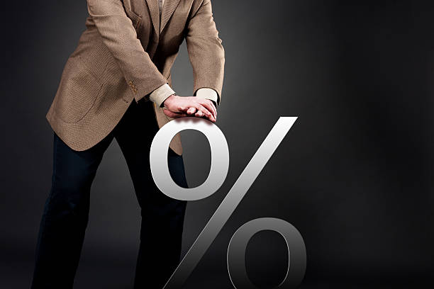 Pushing down interest rate A businessman pushing down or restricting interest rate concept interest rate stock pictures, royalty-free photos & images