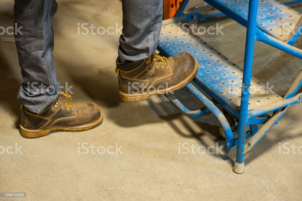Pushing down the safety bar on a rolling ladder stock photo