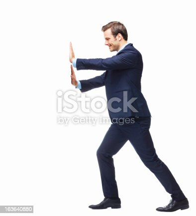 Smiling businessman pressing against a white board - copyspace