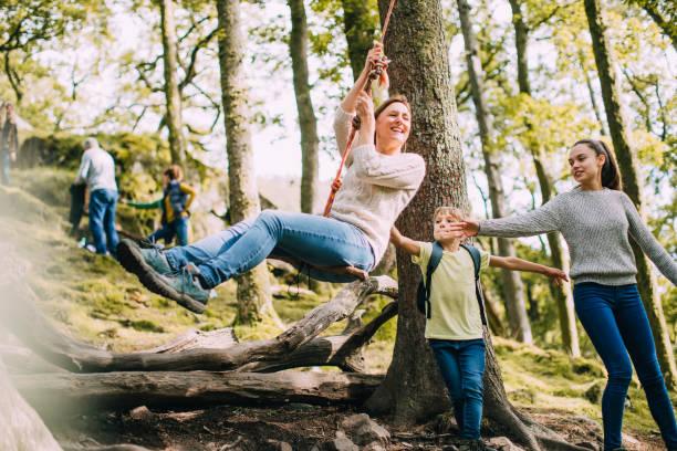 mama te duwen op de rope swing - bos spelen stockfoto's en -beelden