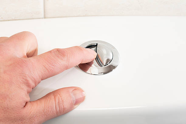 Pushing the flush button on a toilet Mans' hand pushing the flush button on a toilet. flushing water stock pictures, royalty-free photos & images