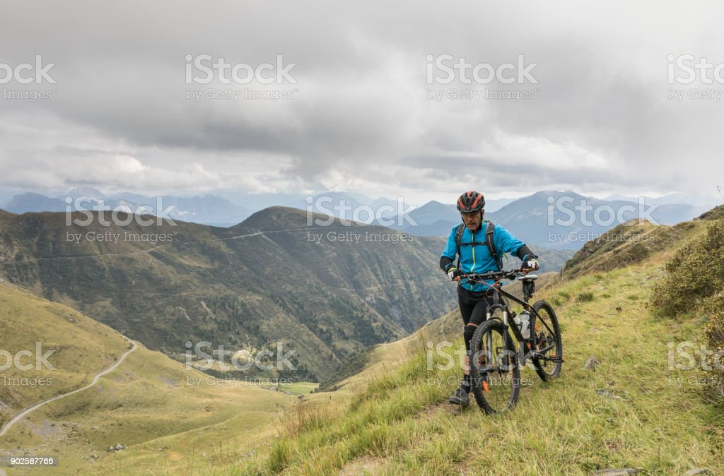 Pushing the mountainbike uphill in th Friulian Mountains, Italy. stock photo