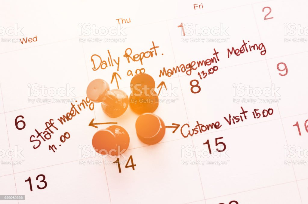 Pushpin on calendar with busy day stock photo