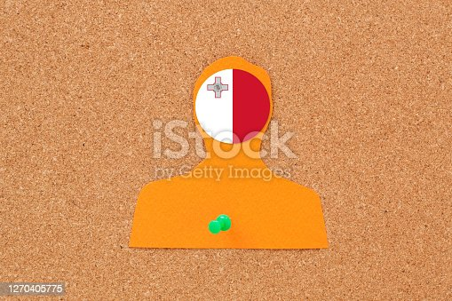 Paper silhouette of male pushpined to cork bulletin board with maltese flag on his head