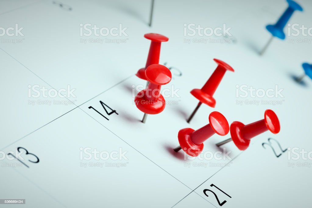 Pushpins on calendar stock photo
