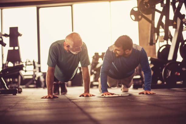 flexiones de brazos en el gimnasio. - entrenador personal fotografías e imágenes de stock