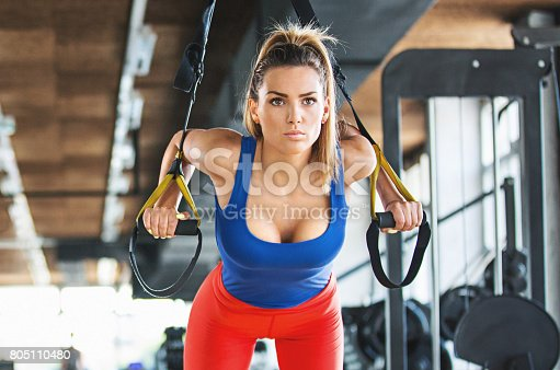 Closeup front view of an attractive mid 20's woman exercising in a gym. She is doing suspension cables training and performing push ups. Looking straight forward, focused. Dressed in a blue tank top and red leggings.