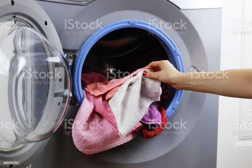 put cloth in washer stock photo