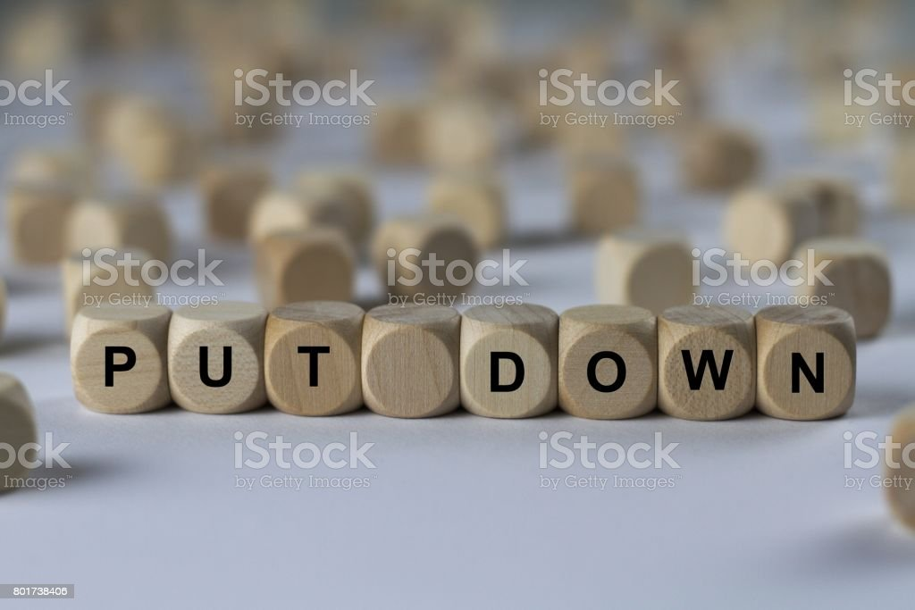 put down - cube with letters, sign with wooden cubes stock photo