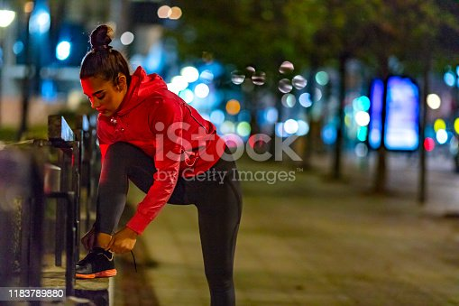 Young woman tying her shoelaces before running on city street at night. Young beautiful athletic girl standing on sidewalk and tying laces during training outdoors at night.