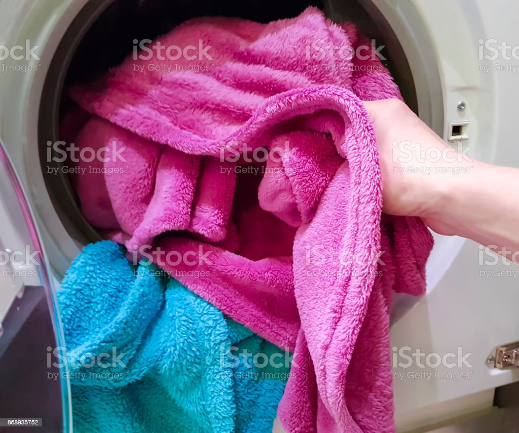 put the cloth in the washer stock photo