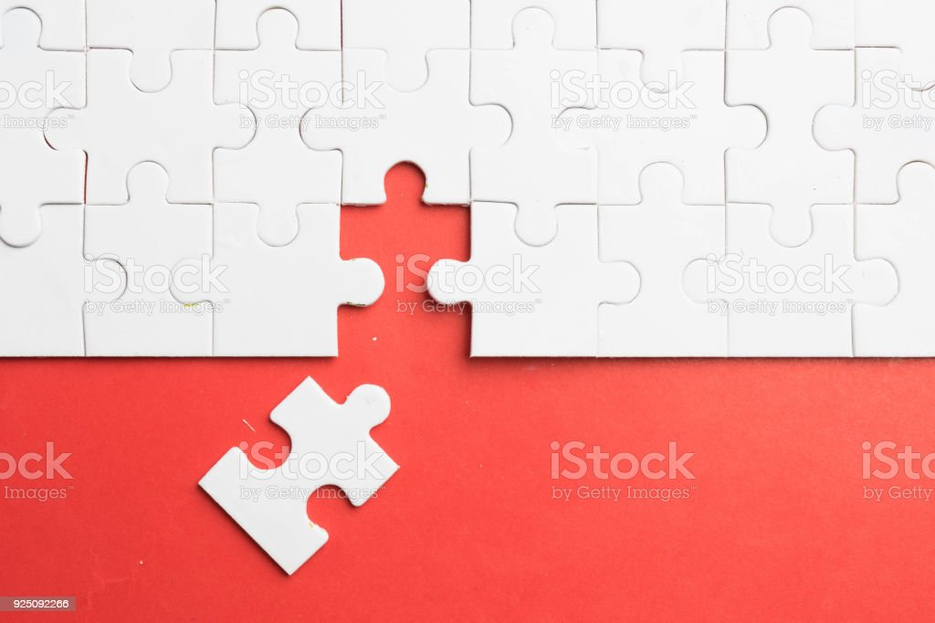 put the last piece of jigsaw puzzle to complete the mission on red background stock photo