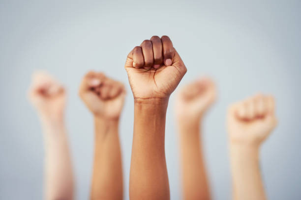 Put the power back in your hands Cropped studio shot of a group of women raising their fists in solidarity against a gray background social issues stock pictures, royalty-free photos & images