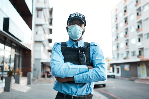 Portrait of a confident masked young security guard standing guard outdoors