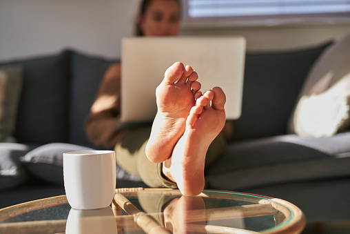 Shot of a young woman using a laptop on the sofa at home with coffee in the foreground