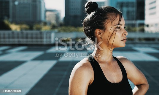 Shot of a sporty young woman taking a break while exercising in the city