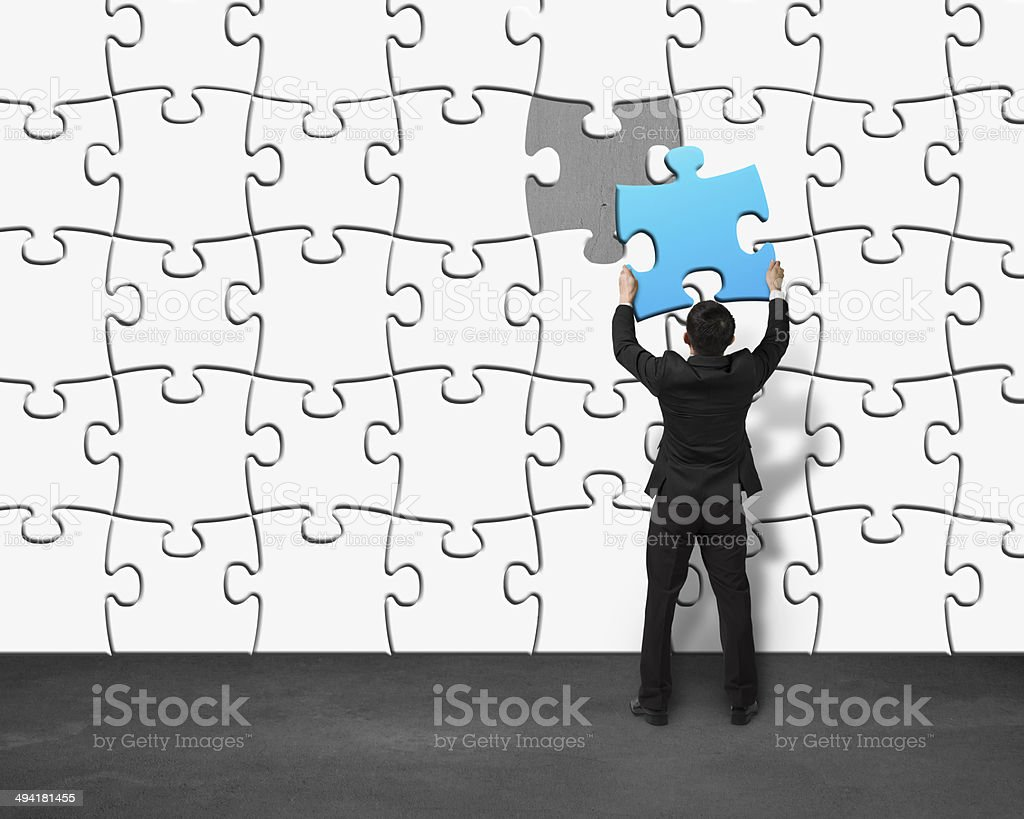 Puting unique blue puzzle into wall stock photo