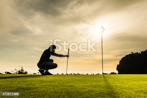 A silhouette of a golfer taking aim at the cup at sunset.  http://blog.michaelsvoboda.com/GolfBanner.jpg