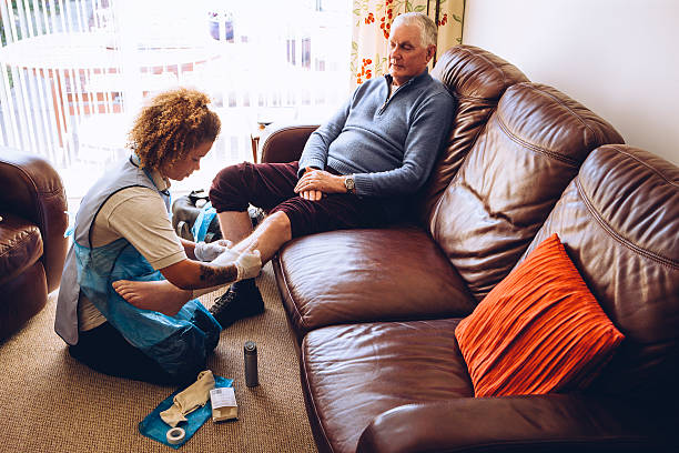 putting a bandage on - old man feet stock photos and pictures