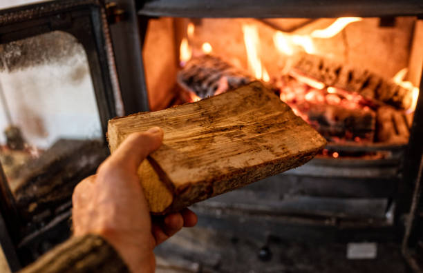Putting a log into a wood burning stove stock photo