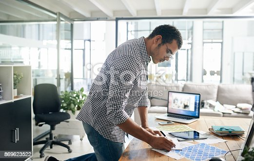 Shot of a young businessman writing notes at his desk in a modern office
