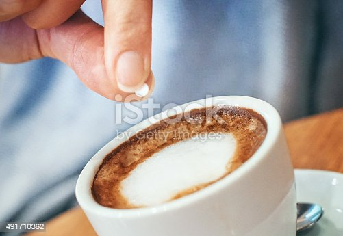 Closeup of unrecognizable woman putting one piece of artificial sweetener into her coffee. These sweeteners are based on aspartame or acesulfam compunds . Tilt shot.