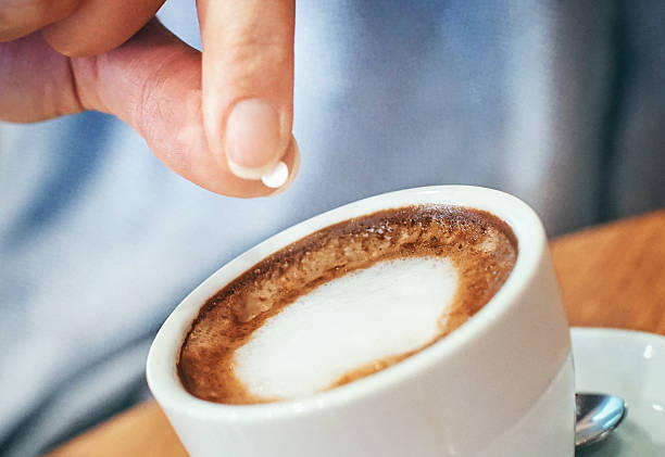 putting artificial sweetener into coffee - sweeteners stock photos and pictures