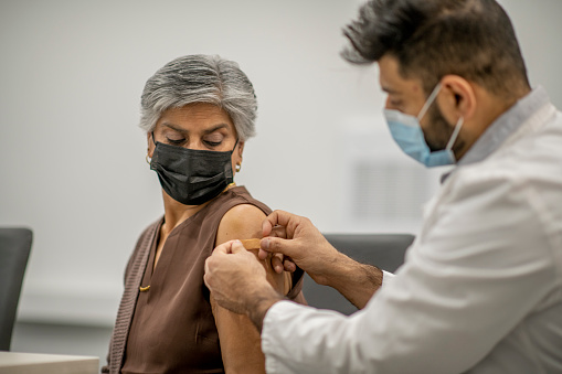 A male doctor puts a band aid on a senior woman's arm after he administered the COVID-19 vaccine injection. They are both wearing a protective face mask to protect themselves from the transfer of germs.