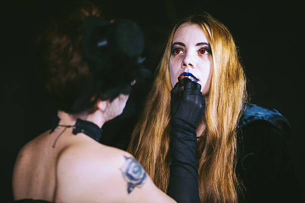 putting blue lipstick for scary halloween party - dracula schminken stock-fotos und bilder