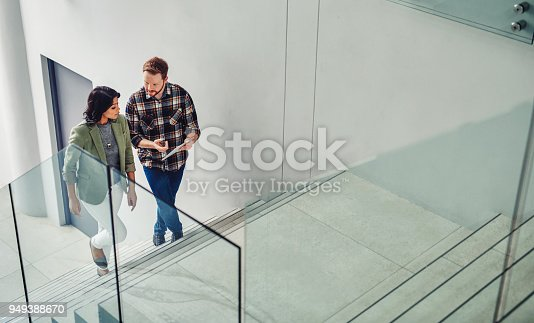 Shot of two young coworkers using a digital tablet while walking up stairs in a modern office