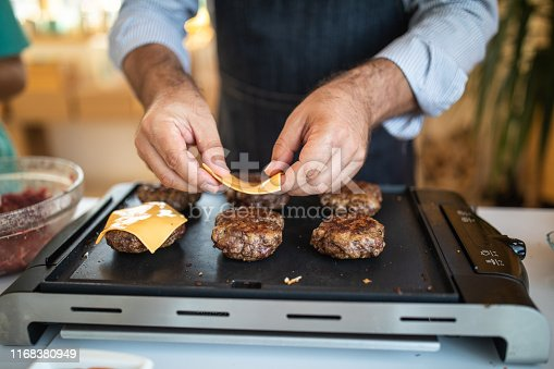 Close up of human hands while unrecognizable man putting cheese on burgers while grilling them on electrical barbecue