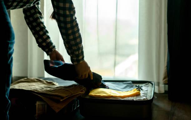 putting kleidung ins reisegepäck - gepäck verpackung stock-fotos und bilder