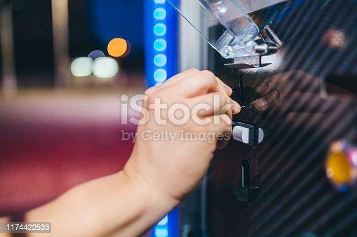 Putting coin in car wash mashine. Close up.