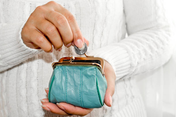 putting coin in purse. Leather purse for coins.  Wallet in hand . Poverty stock photo