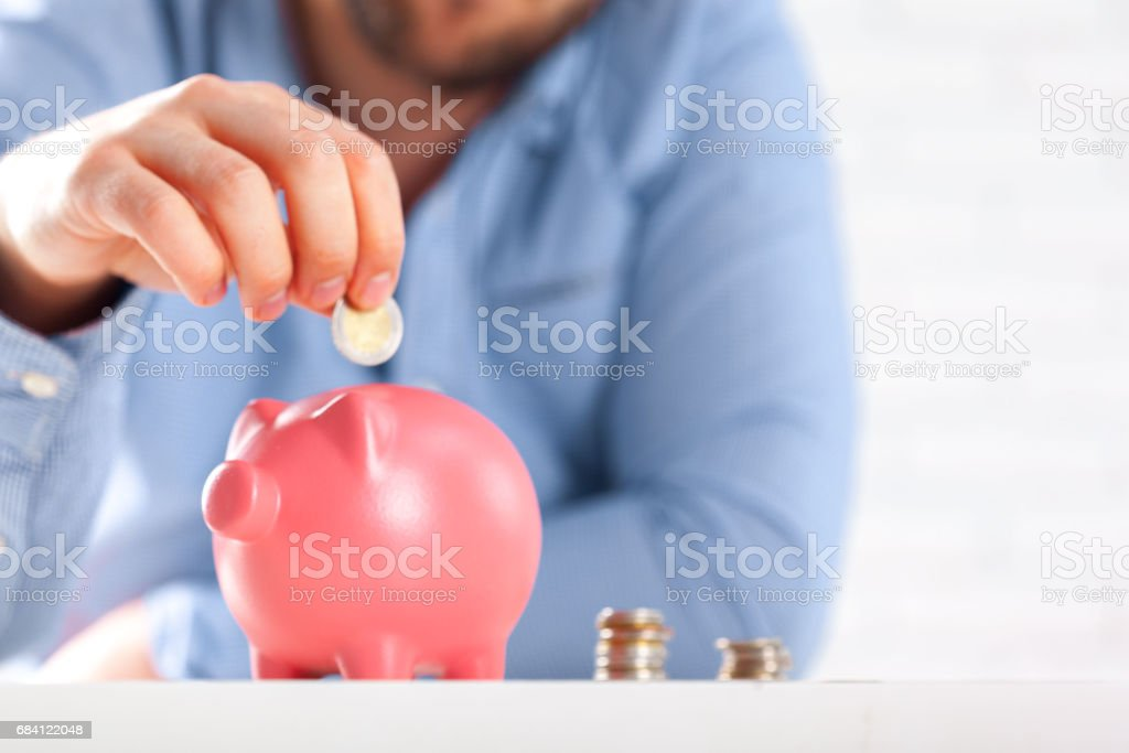 Putting coin into the piggy bank foto stock royalty-free
