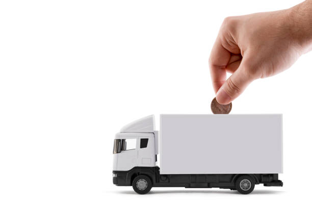 Putting coin into the white cargo delivery truck on white background stock photo