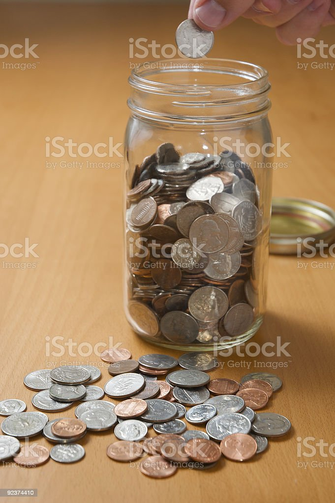 Putting coins into a jar royalty-free stock photo