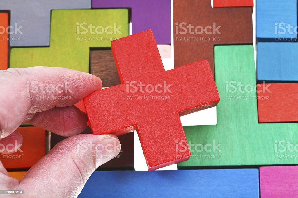 putting cross shaped block in wooden puzzle royalty-free stock photo