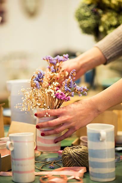 putting trockenen blumen in vase - bastelshop stock-fotos und bilder