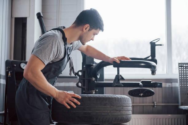 Element in den Reifen legen. Junger Mann arbeitet tagsüber mit Radscheiben in der Werkstatt – Foto
