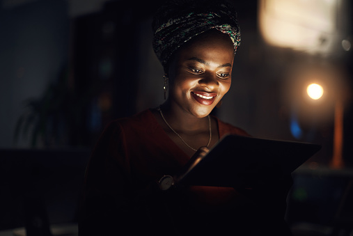 Shot of a young businesswoman using a digital tablet in an office at night