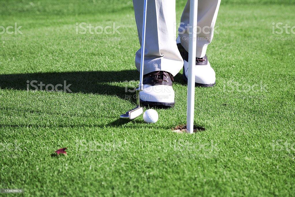 Putting golf ball hole green grass course shoes man