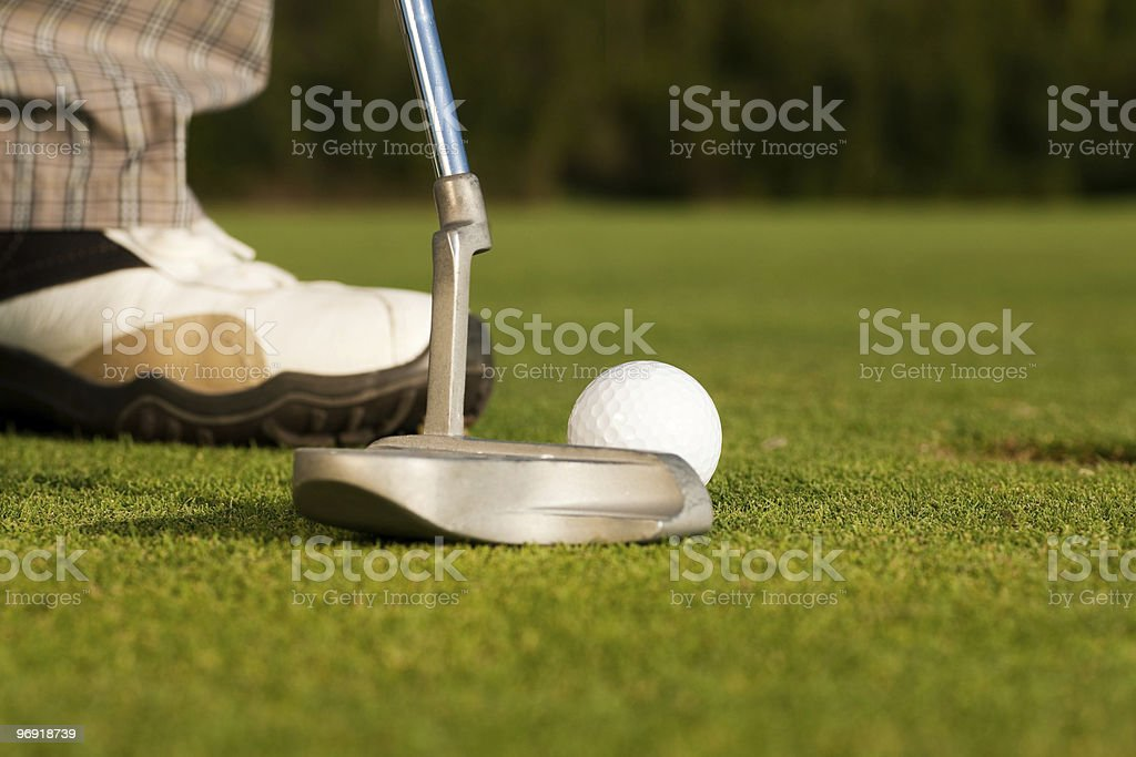 Putting golf ball in cup royalty-free stock photo