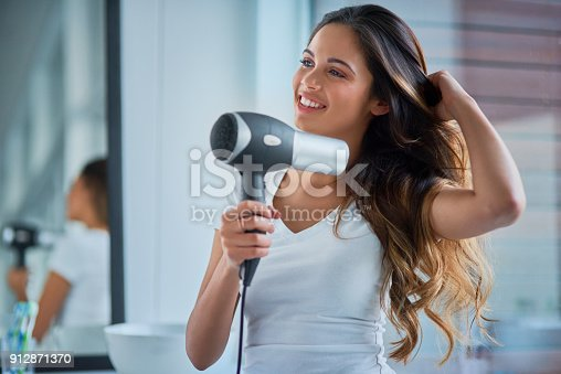 Shot of an attractive young woman blowdrying her hair in the bathroom