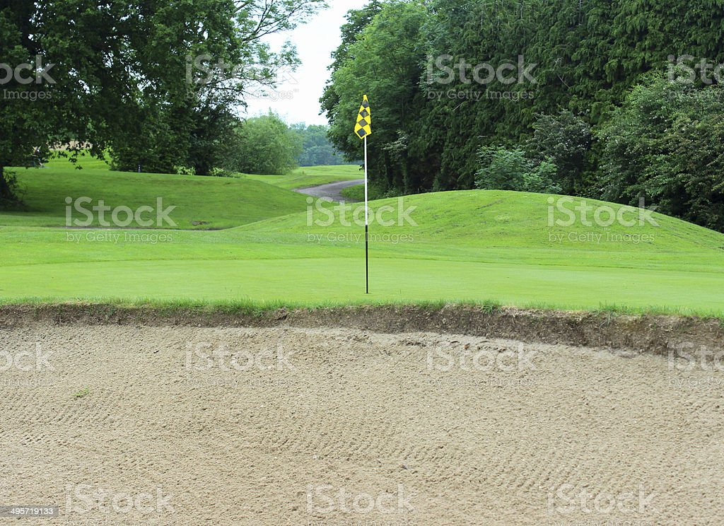 Putting green grass and flag at hole on golf course stock photo