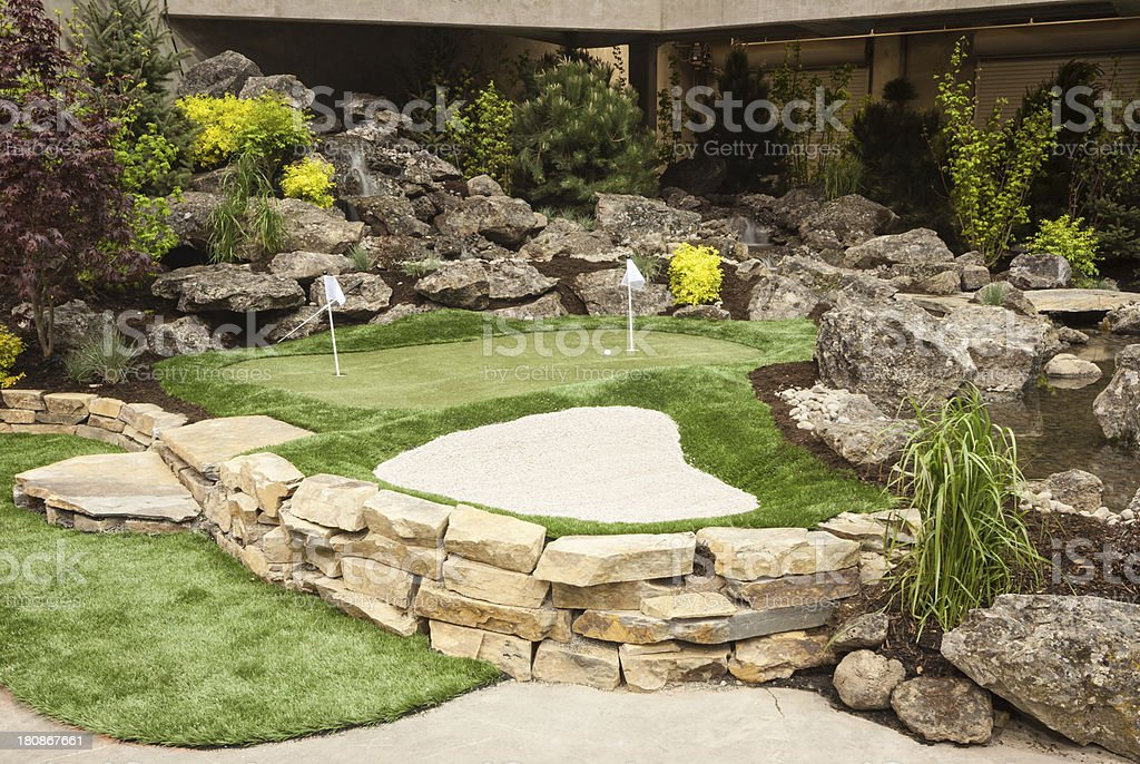 This home back yard has a putting green and a sand pit.