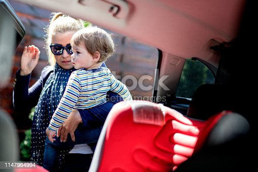 Putting her son in his car seat. Mother and her  son go out.