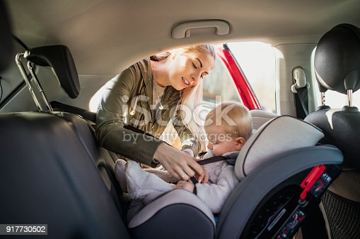 istock Putting Her Son in His Car Seat 917730502