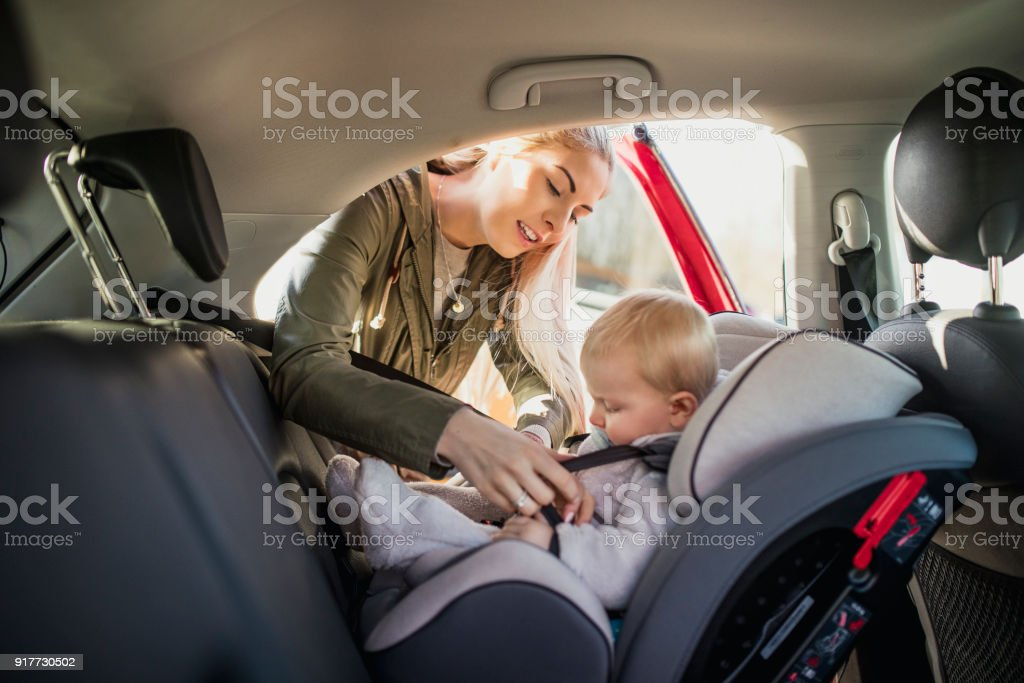 Putting Her Son in His Car Seat stock photo